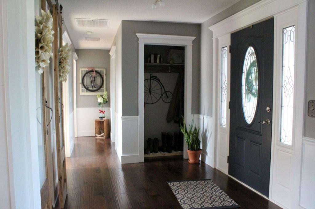 Light and bright foyer--grey walls, white trim, navy door, sliding doors