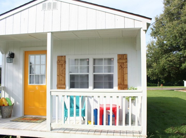 Front of beautiful white she shed with natural wooden shutters and yellow front door