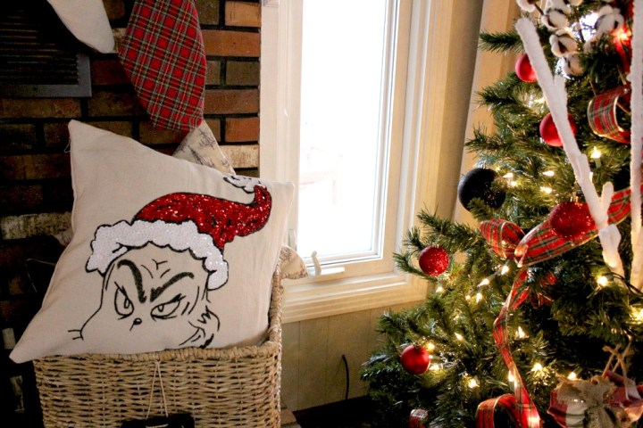 Grinch Pillow cover in basket next to Christmas tree