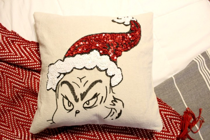 DIY Grinch pillow cover with pillow inserted laying on blanket