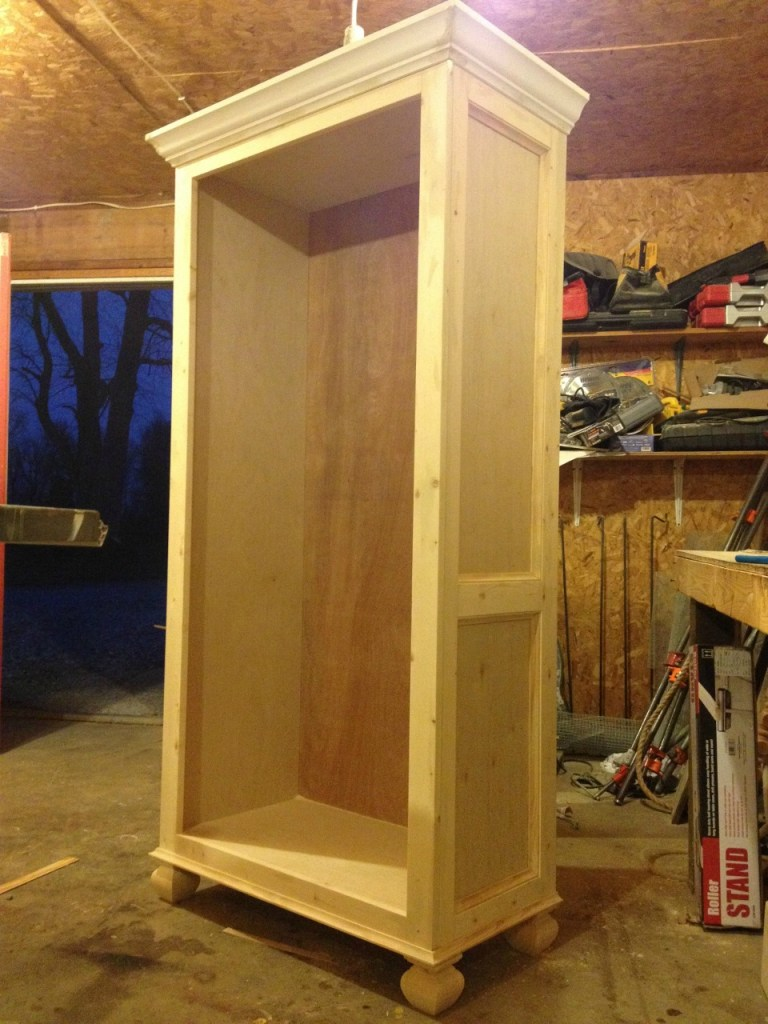 Unfinished tall bookshelf in workshop before adding shelves--trimmed out on the sides with 1x3s and cove molding