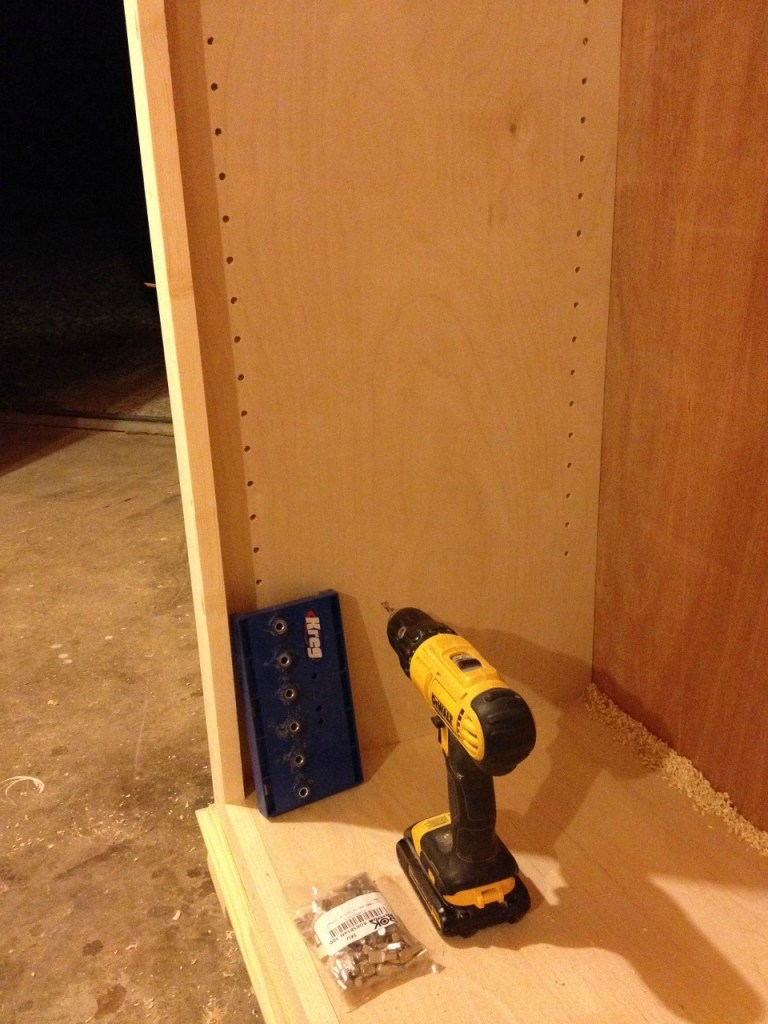 Shelf pins drilled into sides of free standing bookshelf with Kreg shelf pin jig