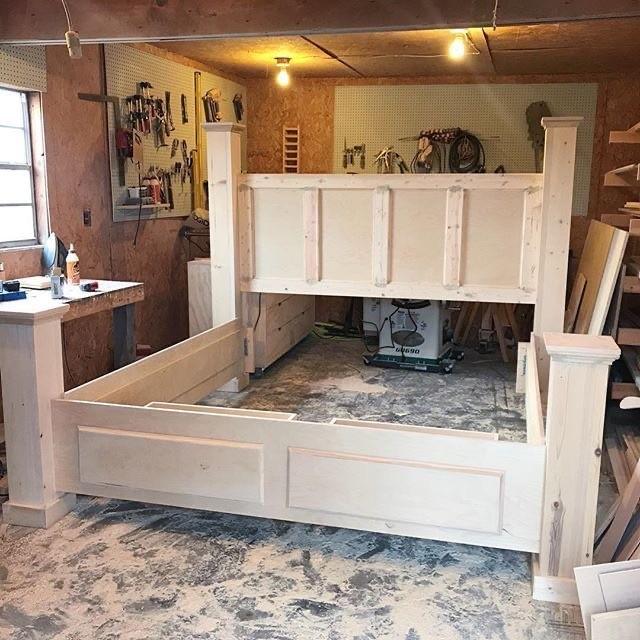 Unfinished DIY storage bed frame in workshop