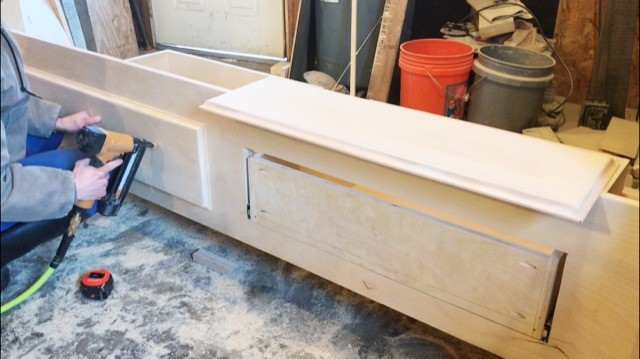 Installing drawer fronts onto drawer boxes in foot board