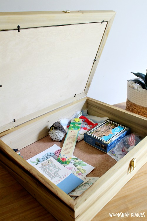 Lid of picture frame box open showing trinkets inside