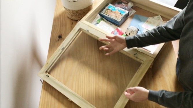 Shara placing glass panel inside picture frame lid