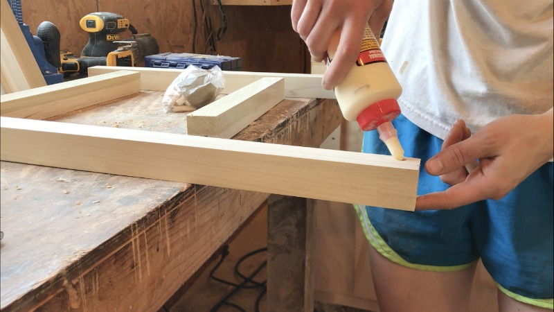 Apply wood glue into dowel holes to glue up nightstand frame