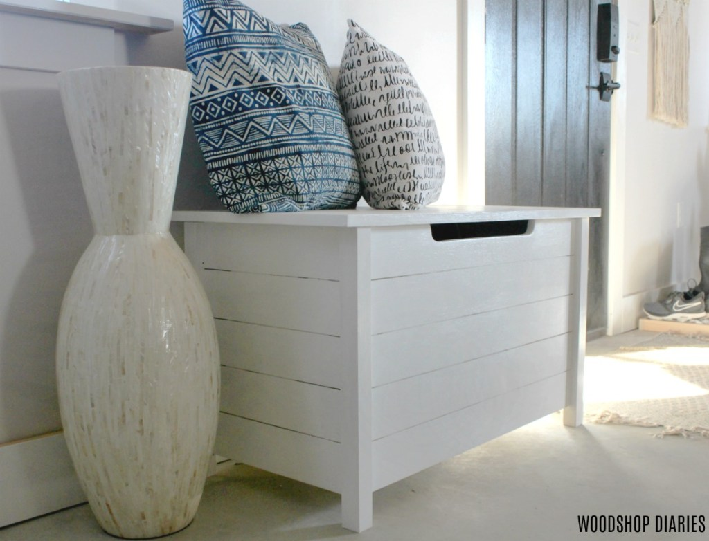 DIY Faux slat toy box painted white used as an entryway bench