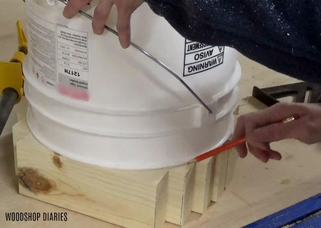 tracing around wood base of DIY concrete planter pot