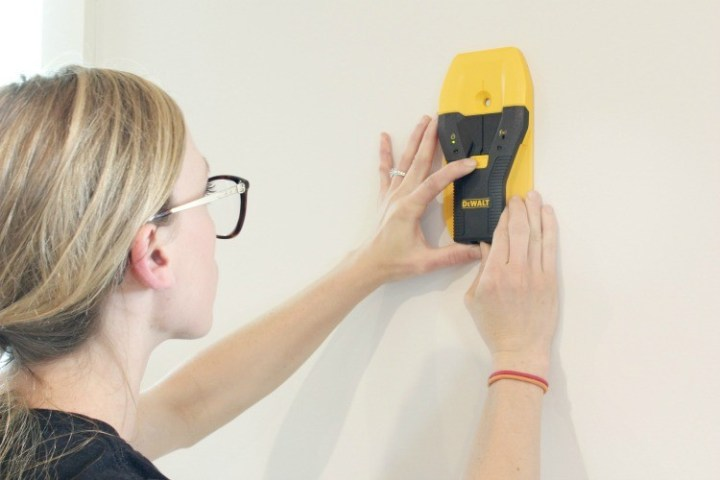 Using stud finder to find studs to hang wall art and shelves--gift idea for new homeowner