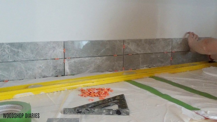 continue adding tiles to backsplash wall