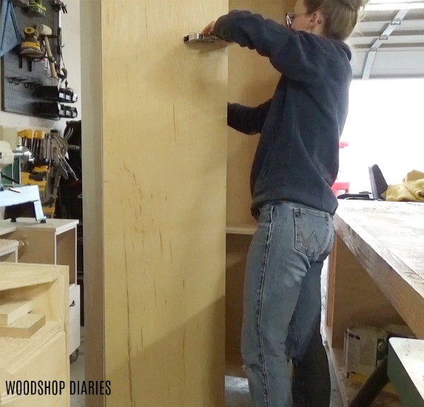 Staple backing onto side cabinet carcasses of DIY Entertainment center