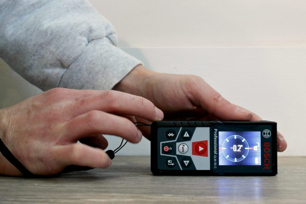 Bosch Blaze Laser Distance Measurer used as a level on flooring surface