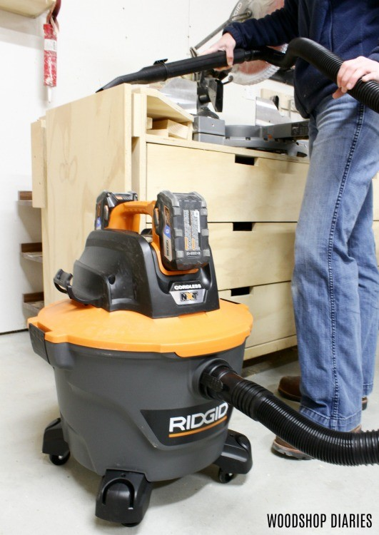 Ridgid 18V Shop Vacuum cleaning sawdust off miter saw stand