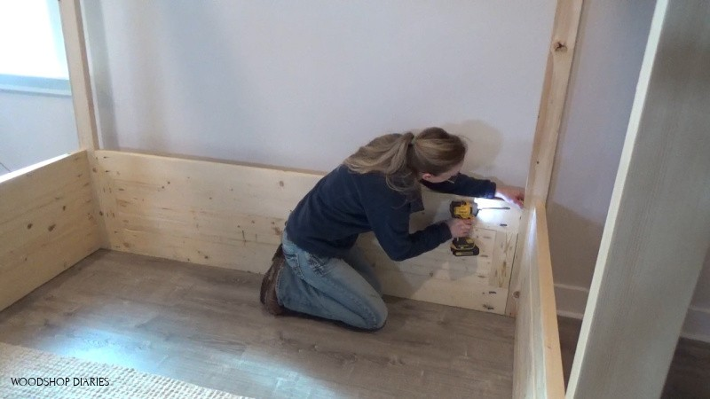 Shara installing back panel of house bed with pocket holes and screws