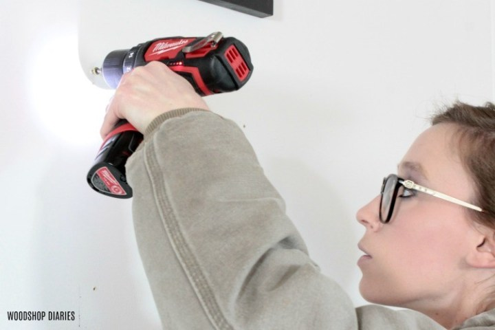 Using battery powered drill to drive screw to hang picture