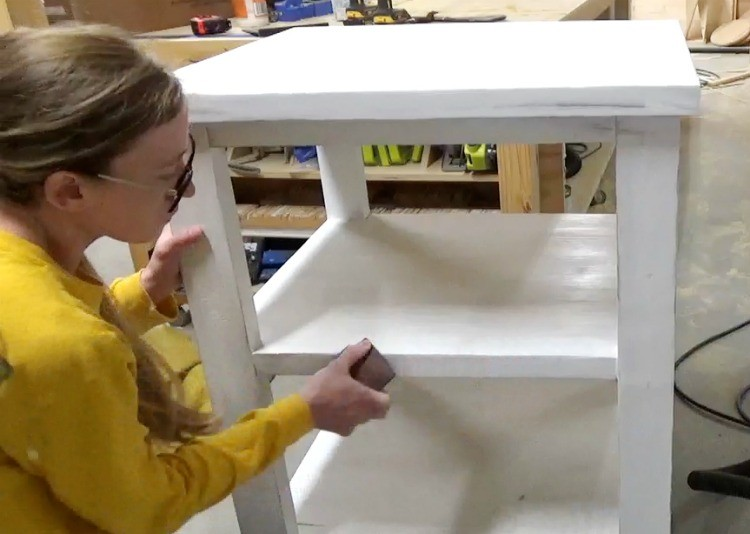 Sanding corners of shelves to give it a farmhouse distressed look