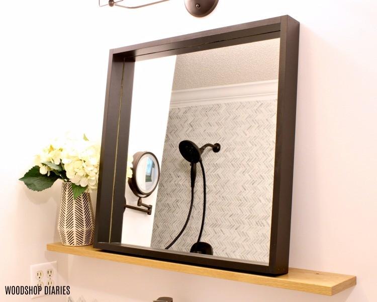 Modern black frame mirror with natural wood floating shelf