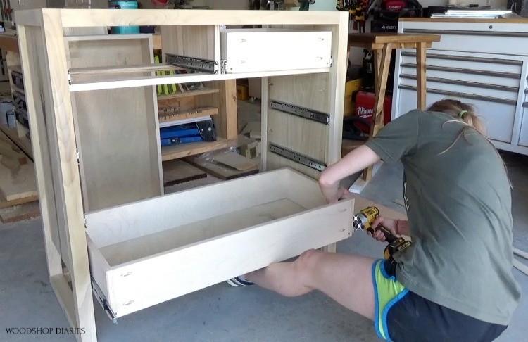 Shara installing bottom dresser drawer into dresser frame using foot as support to hold drawer