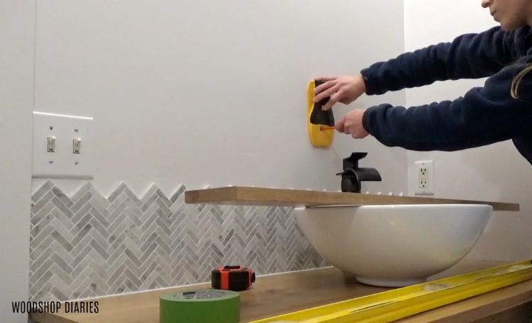 Mark stud locations on wall to install shelf