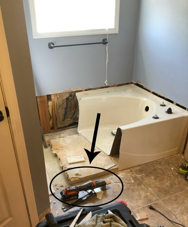 Oscillating saw used to cut through fiberglass tub during bathroom remodel demolition