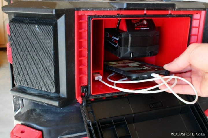 Shara placing phone into weather tight compartment of PACKOUT radio charger
