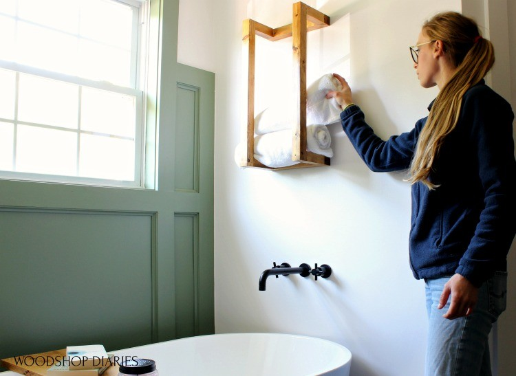 Shara Woodshop Diaries removing towel from scrap wood towel rack hanging on wall above tub