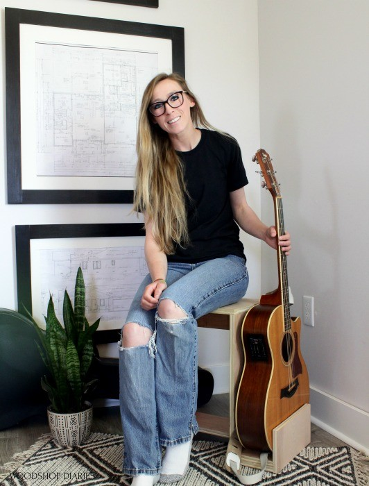 Shara sitting on scrap wood stool holding guitar in stand