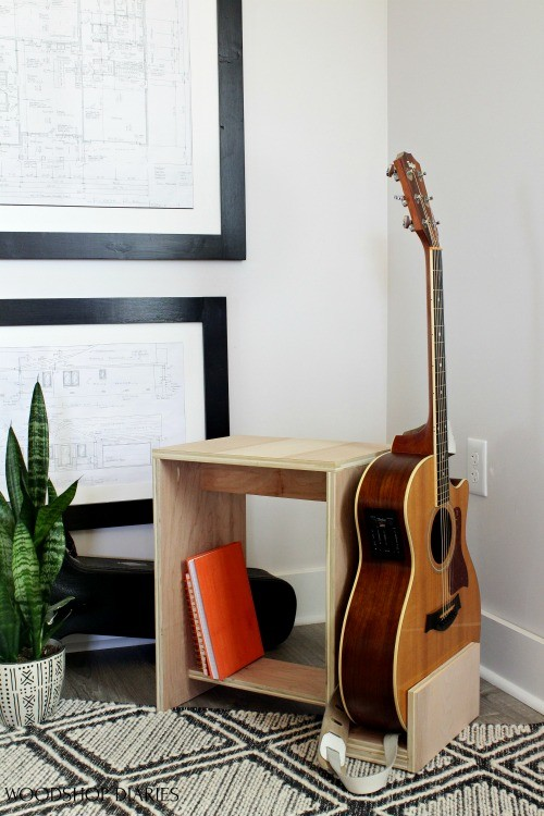 Scrap plywood guitar stand and stool sitting in corner of music room with acoustic guitar in place