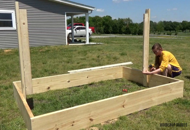 Shara screwing trellis frame into garden bed