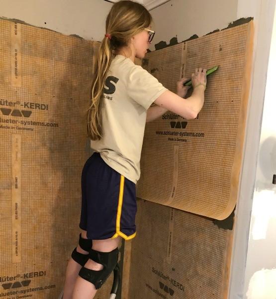 Shara applying Schluter Kerdi to shower walls