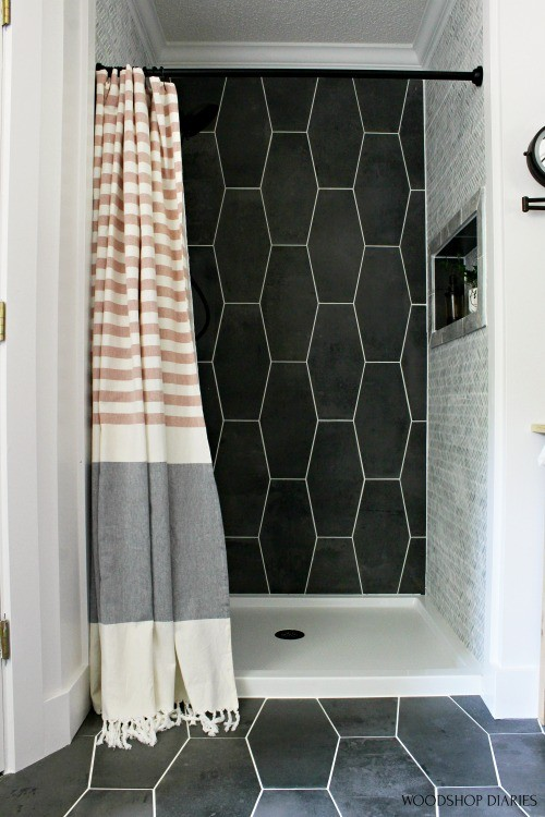 Up close master bathroom shower tile--dark grey back wall and light grey side walls with copper and grey curtain