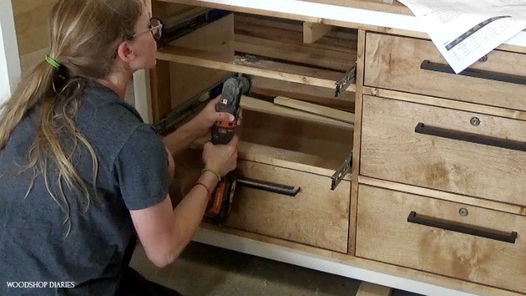 Shara using oscillating saw  to cut slots in dresser frame for lock tab