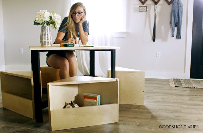 Shara Woodshop Diaries sitting at kids table on one of four storage cubby seats built to slide underneath table