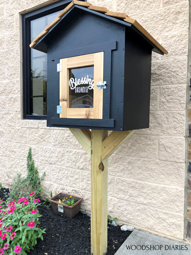 Top to Bottom view of black and cedar blessing birdhouse donation box in front of studio building