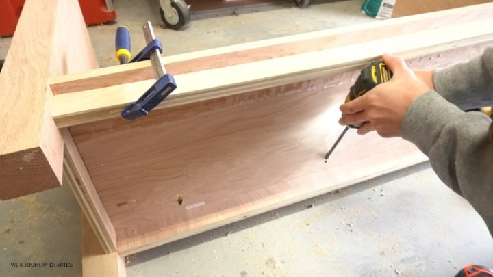 Using pocket holes to screw bottom panel in place in cabinet