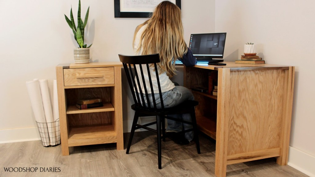 Shara Woodshop Diaries sitting at DIY L shaped desk corner desk with shelves