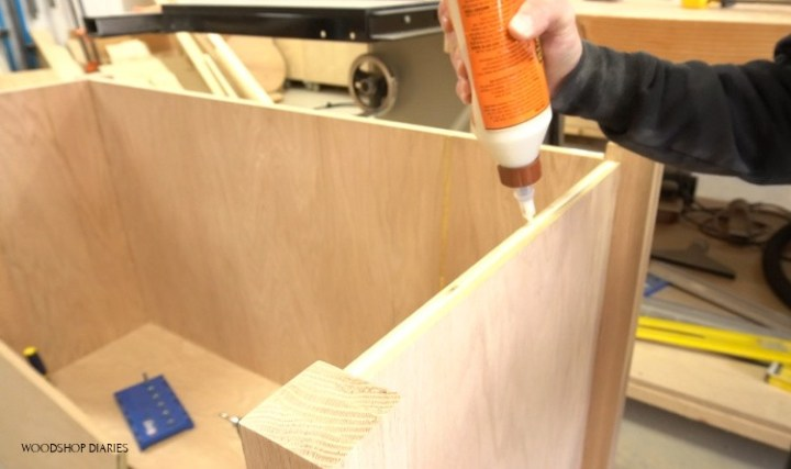 Applying glue to glue end boards in place on corners