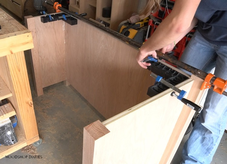 Using corner clamps to glue up right desk cabinet