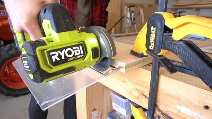 Close up of Ryobi ONE+ HP cut off tool cutting plastic sheet