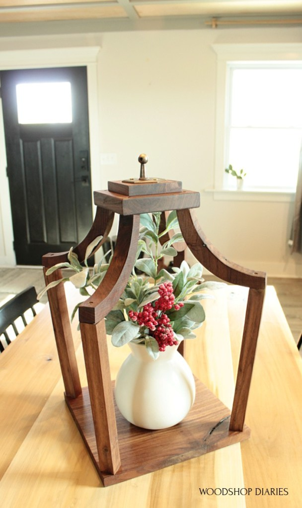 Close up of DIY scrap wood lantern with vase and flower arrangement inside