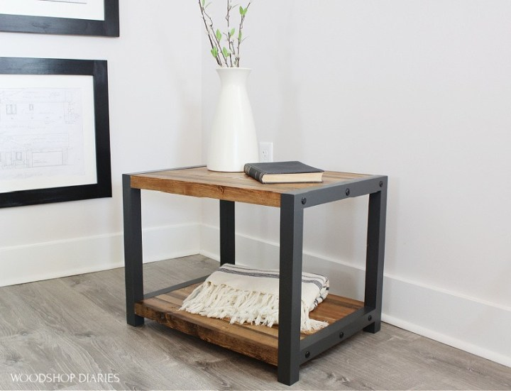 Modern industrial black and wood end table with timber screws on side--staged with vase and book