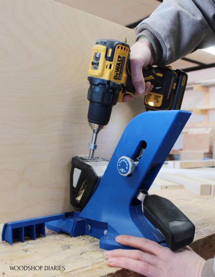 Shara using Kreg 720 pocket hole jig to drill holes in plywood panel
