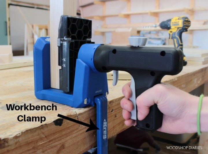 Kreg 520 clamped to workbench with pocket hole clamp and hand clamping the trigger