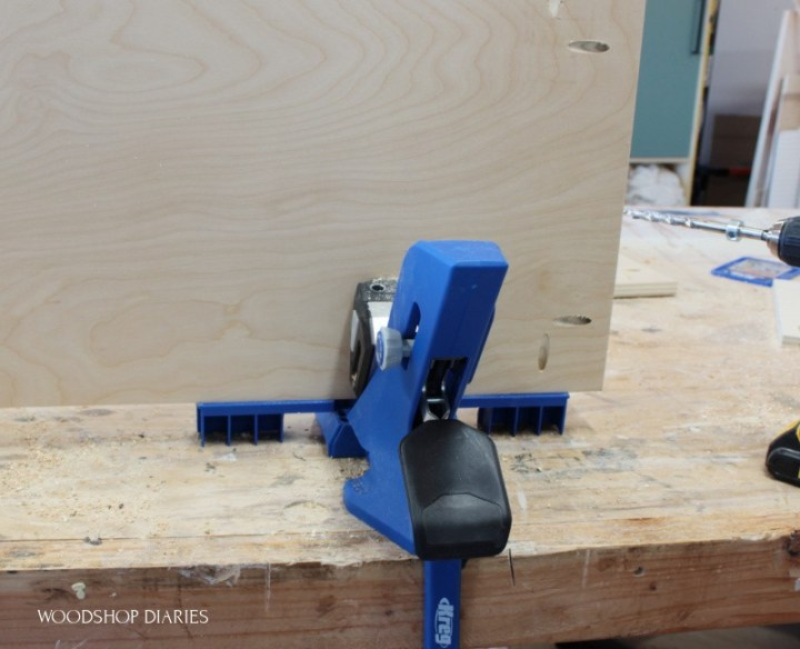 Kreg 720 pocket hole jig with support wings extended and plywood panel clamped in place