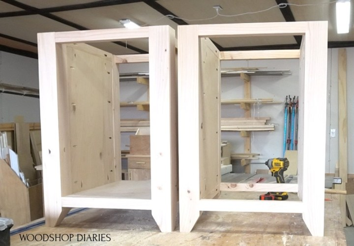 Left and right desk cabinets assembled on workbench--left cabinet with solid bottom and right cabinet with open bottom