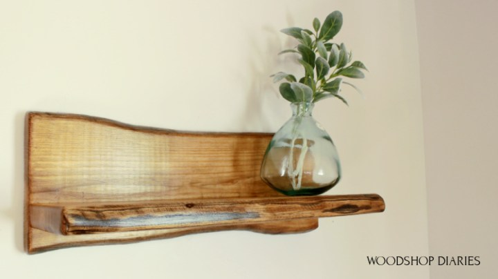 DIY Faux Live Edge Shelf made from pine wood hanging on wall with a glass vase
