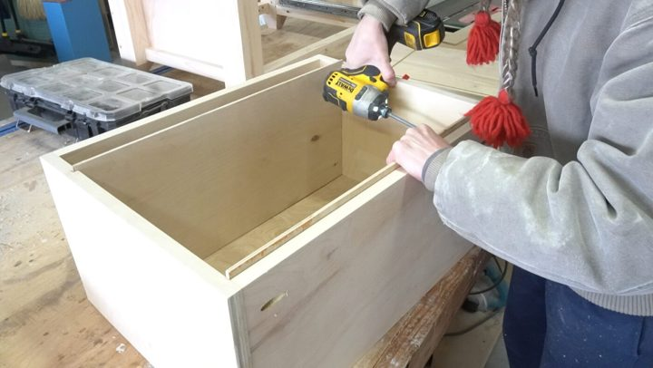 "Shara screwing 1/4"" plywood file folder rails into box"