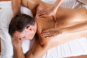 A gentleman receives customized therapeutic back massage at Woodstown Massage Boutique