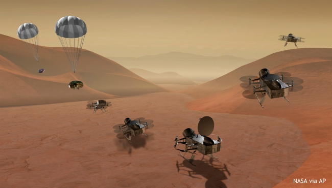 This artist's rendering made available by NASA shows multiple views of the Dragonfly dual-quadcopter lander that would take advantage of the atmosphere on Saturn's moon Titan to explore multiple locations, some hundreds of miles apart. On Thursday, June 27, 2019, NASA announced it would send the drone to the jovian planet's largest moon. Scientists have long considered Titan an attractive place to study whether it would be capable of supporting microbial life. (NASA via AP)